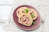 Biscuit roulade with cream and cherries
