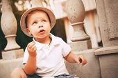 Cute Little Boy In Hat Near Balustrade