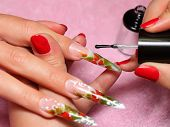 stock photo of nail-design  - Master draws design floral on female nails.