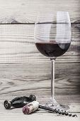 Corks, corkscrew and wine glass on a wooden background