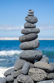stock photo of desert christmas  - Christmas cairn - cairn built of black volcanic stones in a shape of Christmas tree on a beach of black and white pebbles on Fuerteventura Canary Islands Spain ** Note: Soft Focus at 100%, best at smaller sizes - JPG