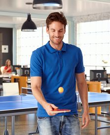 stock photo of ping pong  - Young man playing ping pong in office - JPG