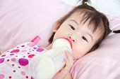 pic of sucking  - Beautiful little asian girl lying and suck up milk bottle in bed - JPG