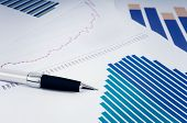 foto of graph paper  - Silver and black pen resting on sheets of paper arranged randomly with bar graphs illustrating financial growth. A graph shows the evolution through the years. The tone is slightly blue.