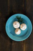 picture of champignons  - champignon mushrooms on a blue plate over a wooden background - JPG