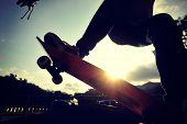 picture of skateboard  - young skateboarder legs skateboarding at sunrise skatepark - JPG