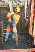 picture of formwork  - builder worker with boom pump pouring concrete on metal rods reinforcement of formwork - JPG