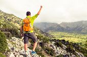 foto of mountain-climber  - Happy climber hiker winning reaching life goal success man at summit successful business concept - JPG