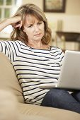 picture of sofa  - Puzzled Mature Woman Sitting On Sofa At Home Using Laptop - JPG