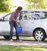 image of car carrier  - Man Washing Car In Drive - JPG