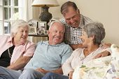 stock photo of retirement  - Group Of Retired Friends Sitting On Sofa At Home Together - JPG
