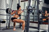 stock photo of fitness-girl  - beautiful sports fitness girl with a barbell in the gym - JPG