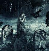foto of ladies night  - Blured transparent ghost of beautiful woman widow in black dress praying on night cemetery - JPG