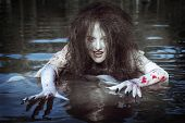 stock photo of bloody  - Beautiful witch woman dressed white bloody shirt standing in the river - JPG