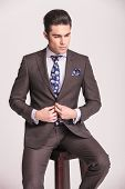 picture of button down shirt  - Handsome business man looking down while closing his suit - JPG