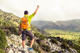 stock photo of climb up  - Happy climber hiker winning reaching life goal success man at summit successful business concept - JPG