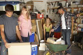 image of yard sale  - Teenage Family Clearing Garage For Yard Sale - JPG