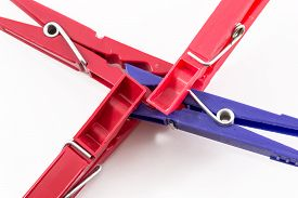 picture of pegging  - Three red pegs attacking and biting a blue plastic peg - JPG