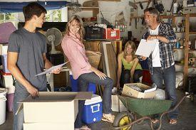 foto of yard sale  - Teenage Family Clearing Garage For Yard Sale - JPG