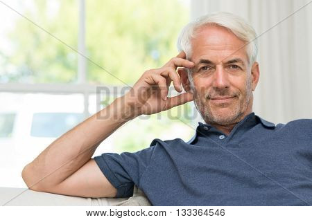 Portrait of a happy senior man relaxing at home. Retired mature man sitting on couch and looking at