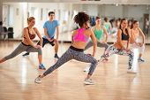 Young group of fitness exercisers in colorful sport clothes with female instructor in fitness class  poster