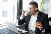 Portrait Of Young Businessman Working On His Lunch Time In Modern Coffee Shop poster