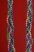 picture of mardi-gras  - mardi gras beads over red can be used as a background / design element