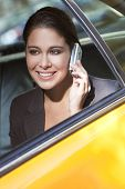 Young Woman Talking On Cell Phone In Yellow Taxi