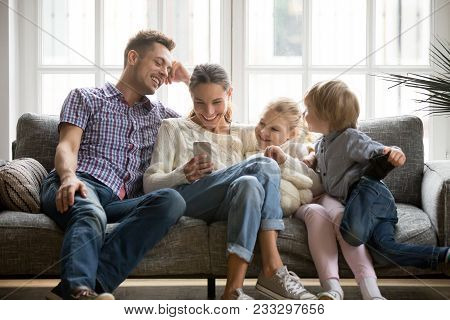 poster of Cheerful Young Family With Kids Laughing Watching Funny Video On Smartphone Sitting On Couch Togethe