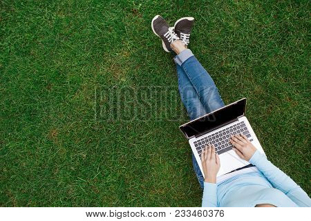 poster of Top View Of Girl Sitting In Park On The Green Grass With Laptop, Hands On Keyboard. Copy Space On Co