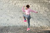 Joyful Sporty Latin Girl Jumping High And Raising Knee. Street Dancer Warming Up Intensively Before  poster