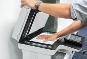Close Up Businessman Use Printer Glass Plate To Scan Important And Confidential Documents In Office poster