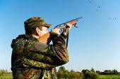 Male hunter in camouflage clothes on the field aiming and shooting with hunting rifle to gamebird du