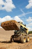 stock photo of skid  - skid steer loader moving sand soil at construction area outdoors - JPG