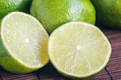 Lime Citrus Fresh Fruits On Wooden Table. Close Up Shot Of Limes. Focus On The Central Part Of Slice poster