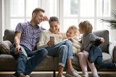 Cheerful Young Family With Kids Laughing Watching Funny Video On Smartphone Sitting On Couch Togethe poster