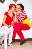 Pretty Girl Whispering Gossips In Ear Of Her Interested Girlfriend