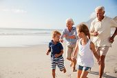 Grandparents Running Along Beach With Grandchildren On Summer Vacation poster