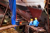 KUCHING, BORNEO ISLAND - MAY 13: Shipyard workers repair a ship in the dry dock beside the Sarawak R