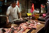 KUALA LUMPUR - MAY 22: Fishmonger in a traditional Chinese wet market works at his stall on May 22,