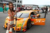 SEPANG - JUNE 19:apr's race queen carries the team's placard at the start of the Japan SUPER GT Round 3 race in Sepang International Circuit on June 19, 2011 in Sepang, Malaysia.
