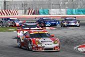 SEPANG, MALAYSIA - JUNE 19: GT cars take turn 1 in tight formation at the Sepang International Circu