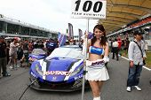 SEPANG, MALAYSIA - JUNE 19: Team Kunimitsu's race queen poses in front of the team car at the Sepang