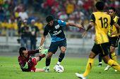 BUKIT JALIL - 13 de julho: Carlos Vela do Arsenal (azul) assume o keeper do objetivo da Malásia antes de scorin
