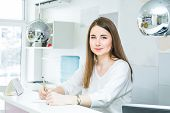 Portrait Of Friendly Young Woman Looking At Camera, Writing Note Behind The Reception Desk. Administ poster