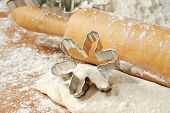 Snowflake cookie cutter with wooden rolling pin and cookie dough dusted with flour.   Macro with sha