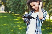 Attractive Young African-american Woman Photographing Outdoors, Watching Pictures On Professional Ca poster