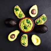 Avocado With Guacamole Sauce In A Bowl On Black Background, Top View. Whole And Half Of Avocado. Gua poster