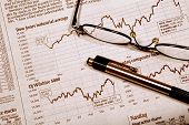 pic of bifocals  - Pair of glasses and a pen resting on a stock market report - JPG