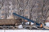 Snow Cleaning Tractor Snow-removal Machine Loading Pile Of Snow On A Dump Truck. Isolate. Snow Plow  poster